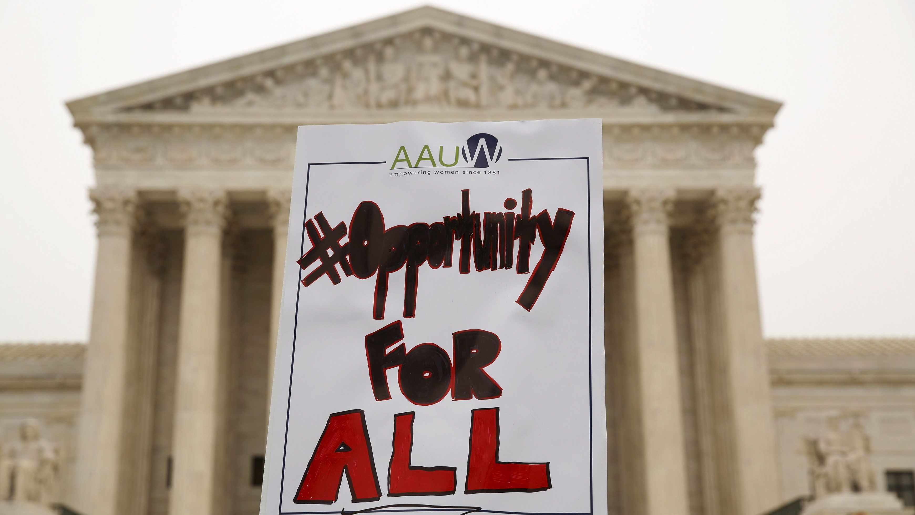 A demonstrator holds a sign aloft as the affirmative action in university admissions case was being heard at the Supreme Court in Washington, DC, on December 9, 2015.