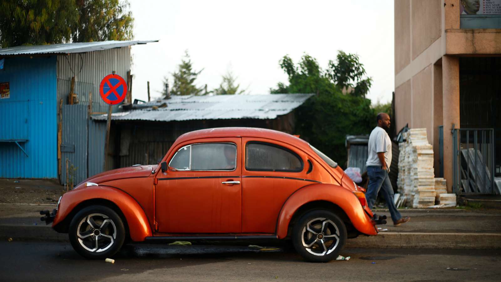 A man walks past a Volkswagen Beetle car parked on a street in Addis Ababa, Ethiopia, September 8, 2017.