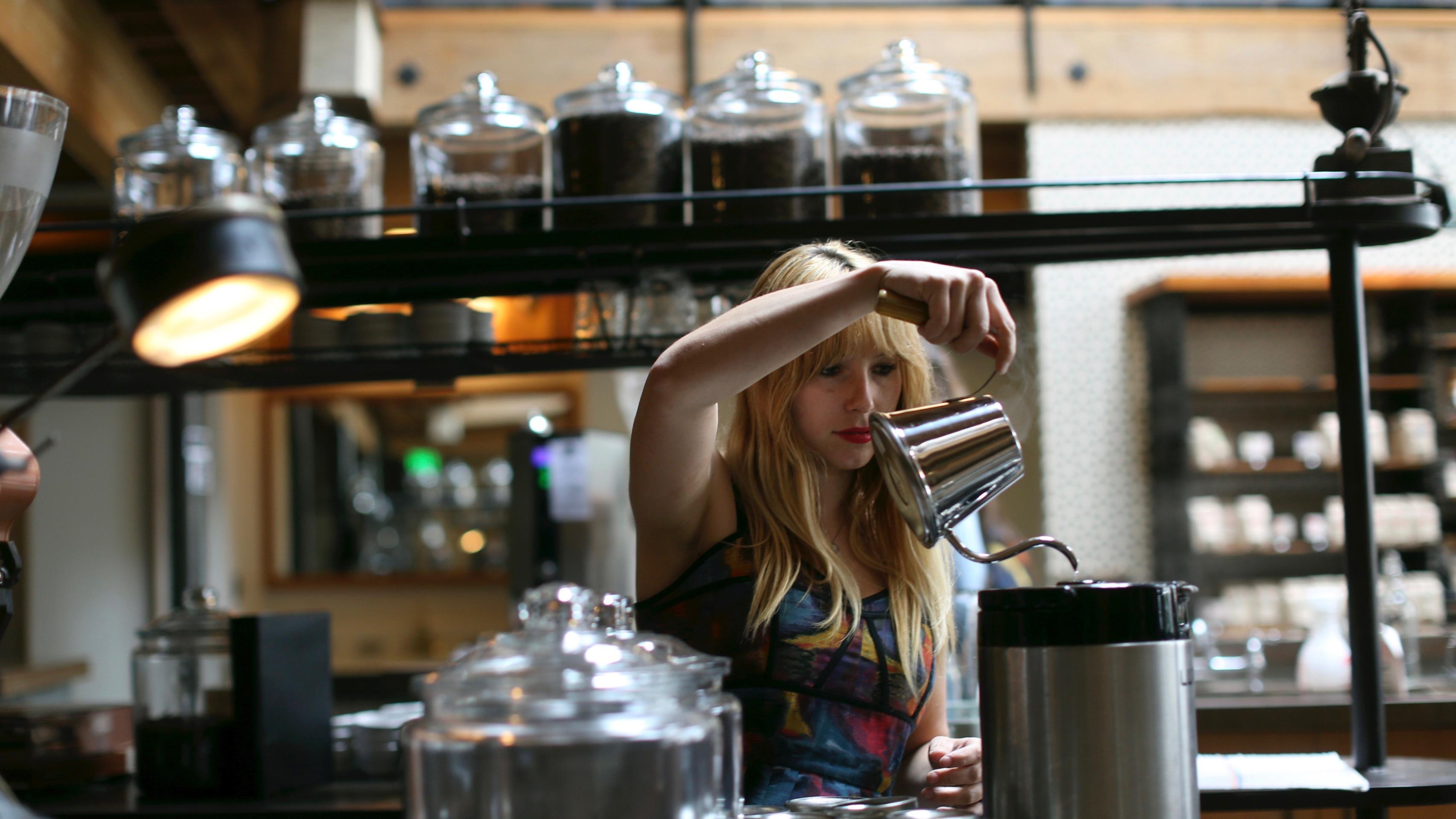 A barista prepares a coffee.