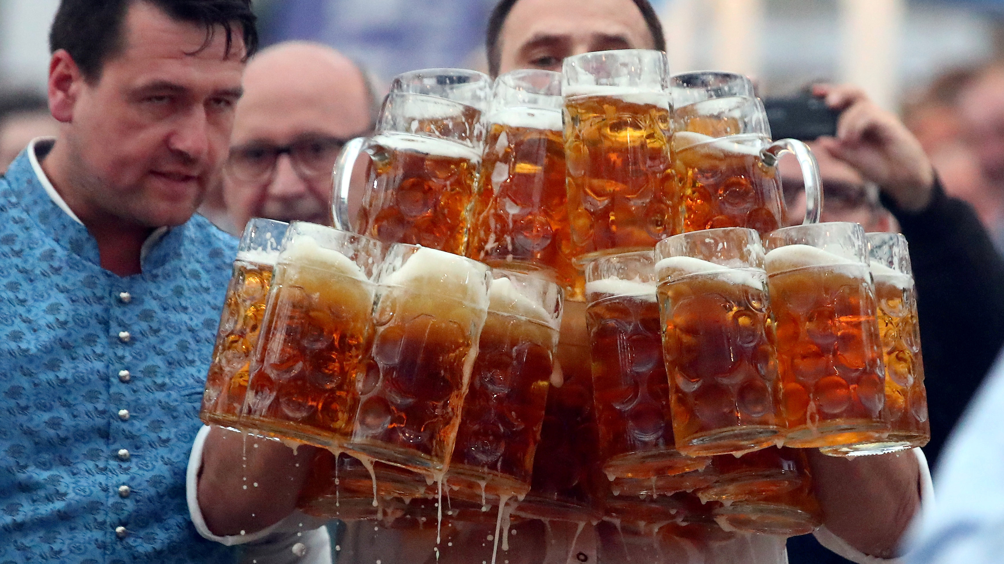 German Oliver Struempfel competes to set a new world record in carrying one liter beer mugs over a distance of 40 m (131 ft 3 in) in Abensberg, Germany September 3, 2017. Struempfel carried 29 mugs over 40 meters to set a new world record. REUTERS/Michael Dalder     TPX IMAGES OF THE DAY - RC18CAE8AC60