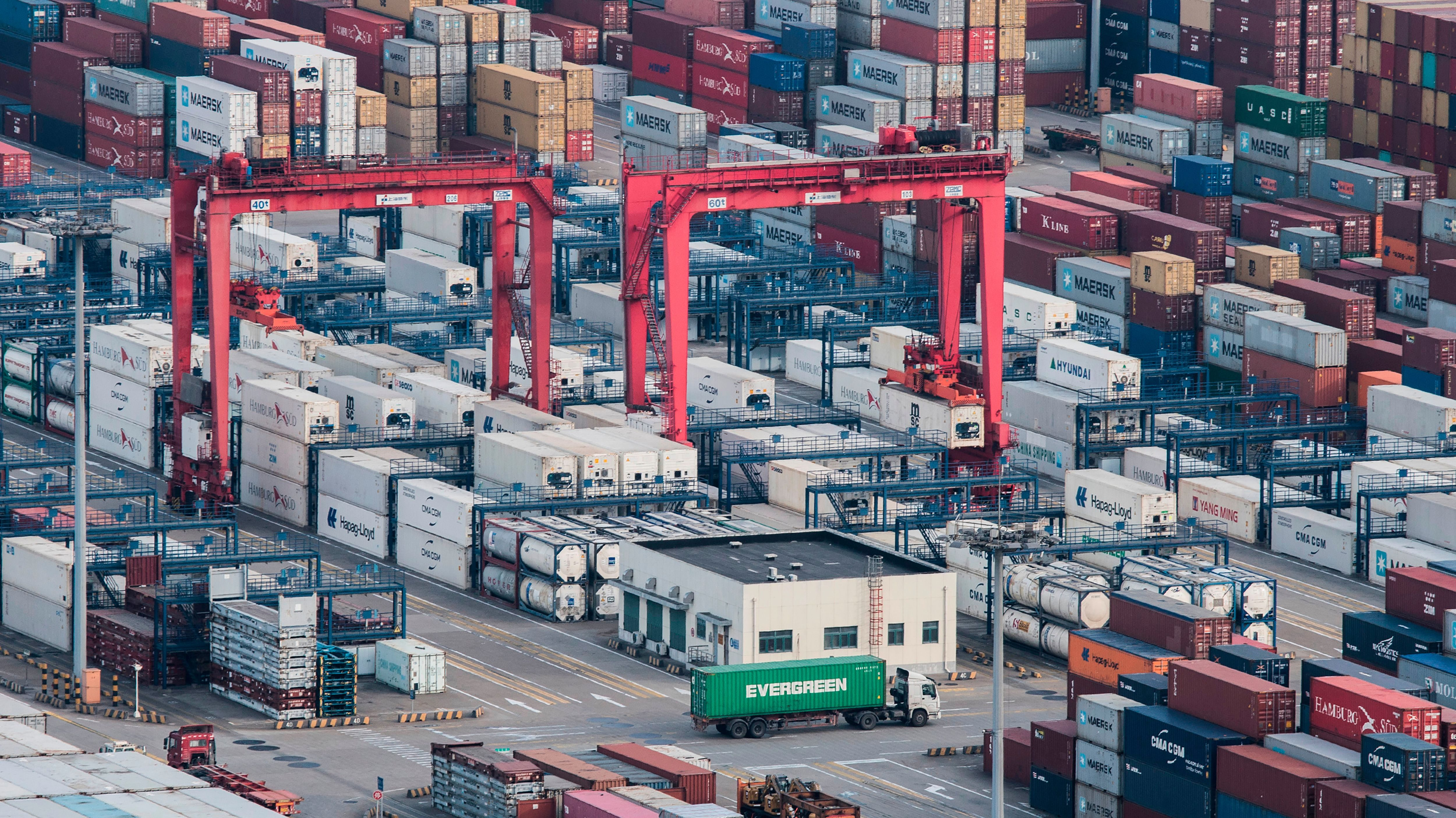 In this March 29, 2018 photo, a cargo truck drives amid stacked shipping containers at the Yangshan port in Shanghai.  China's global trade balance swung to a rare deficit in March as exports shrank but its surplus with the United States, the center of a worsening dispute with Washington, stood at $15.4 billion.