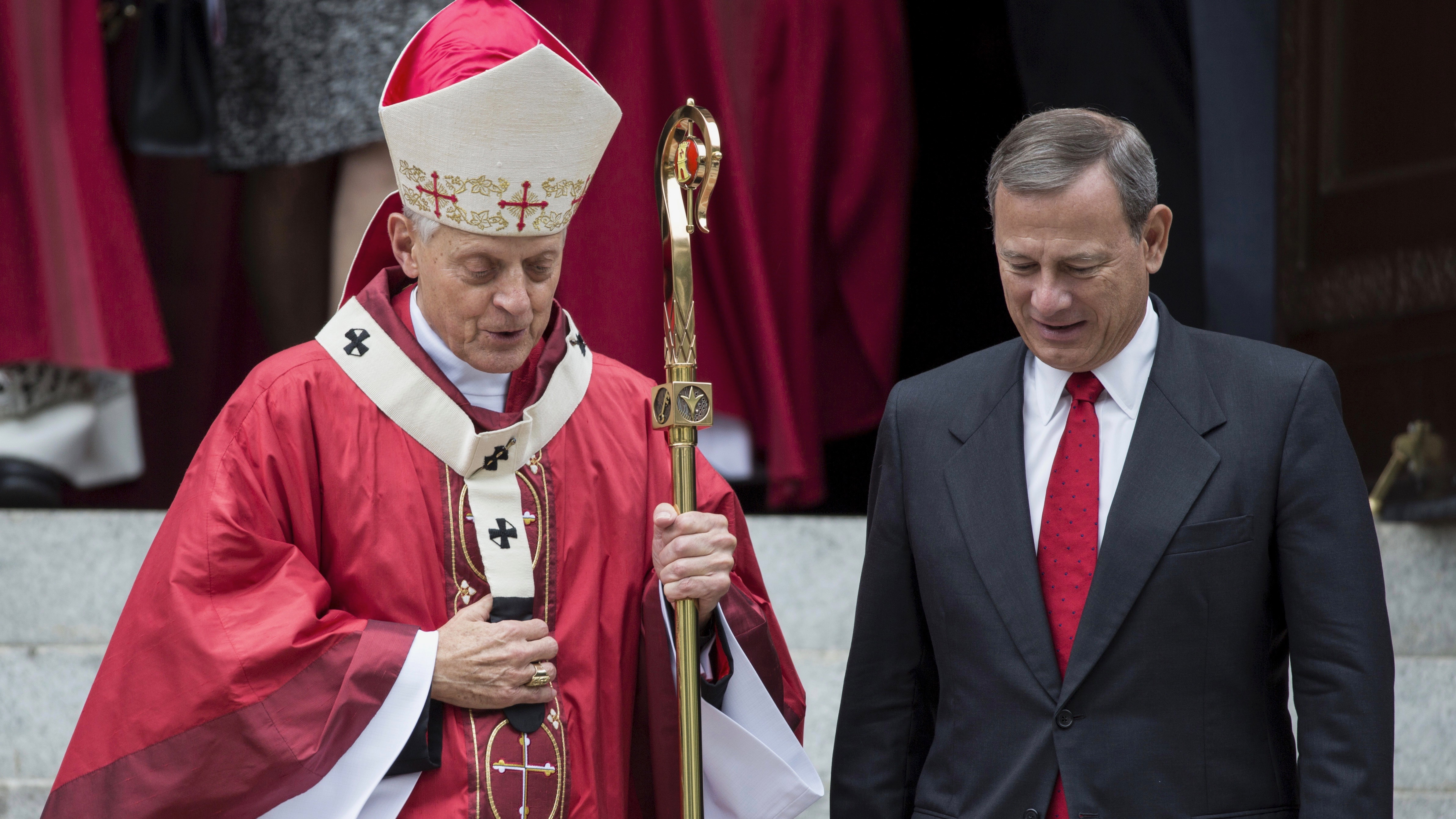 Supreme Court Justice John Roberts (R) speaks with Cardinal Donald Wuerl (L), archbishop of Washington on October 4, 2015.