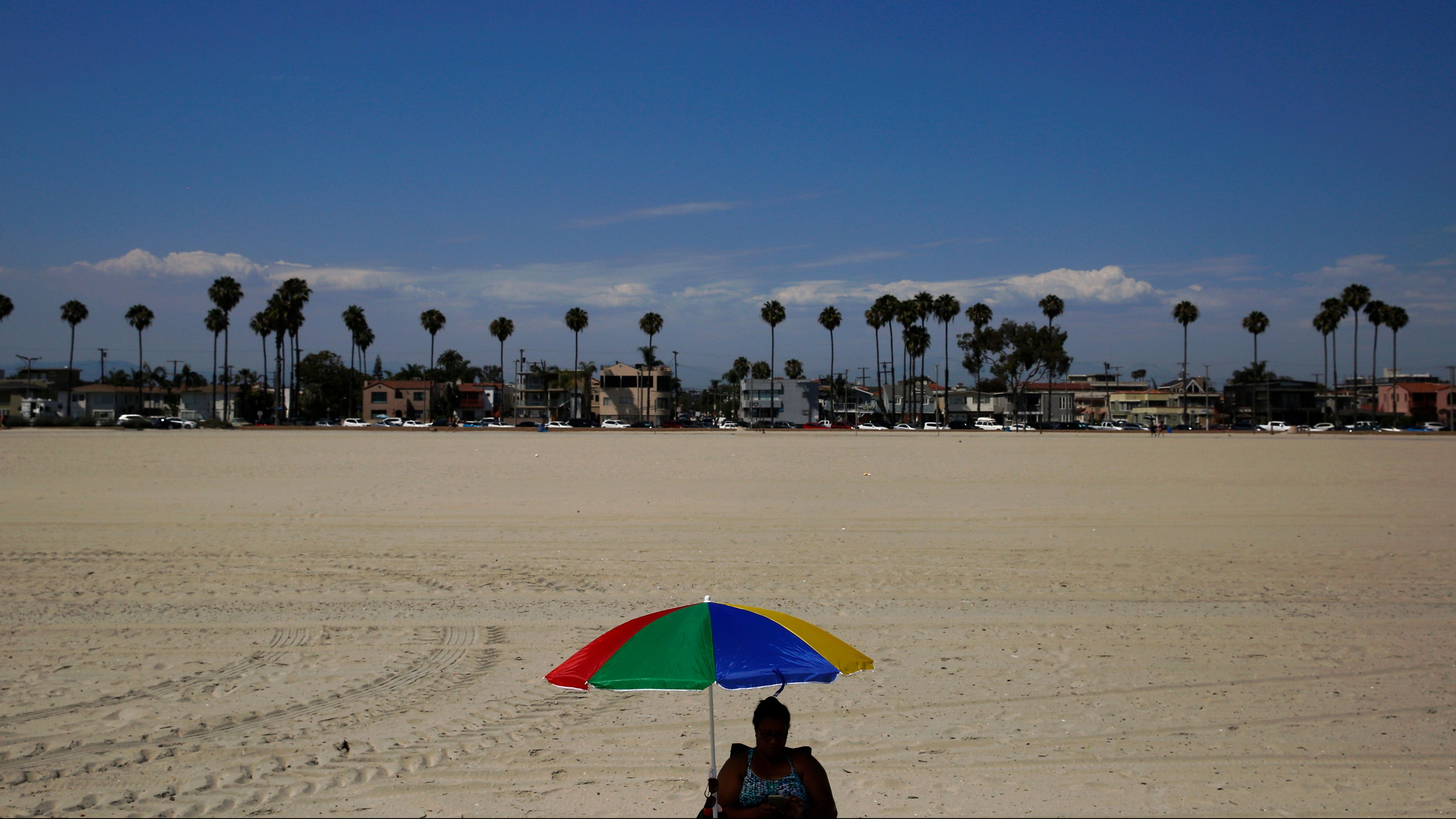 Angie Segi, 48, sits under an umbrella on the beach Friday, July 6, 2018, in Long Beach, Calif. Southern California sizzled Friday in record-breaking heat from the desert to the sea, with widespread triple-digit highs and withering conditions that stoked wildfires.