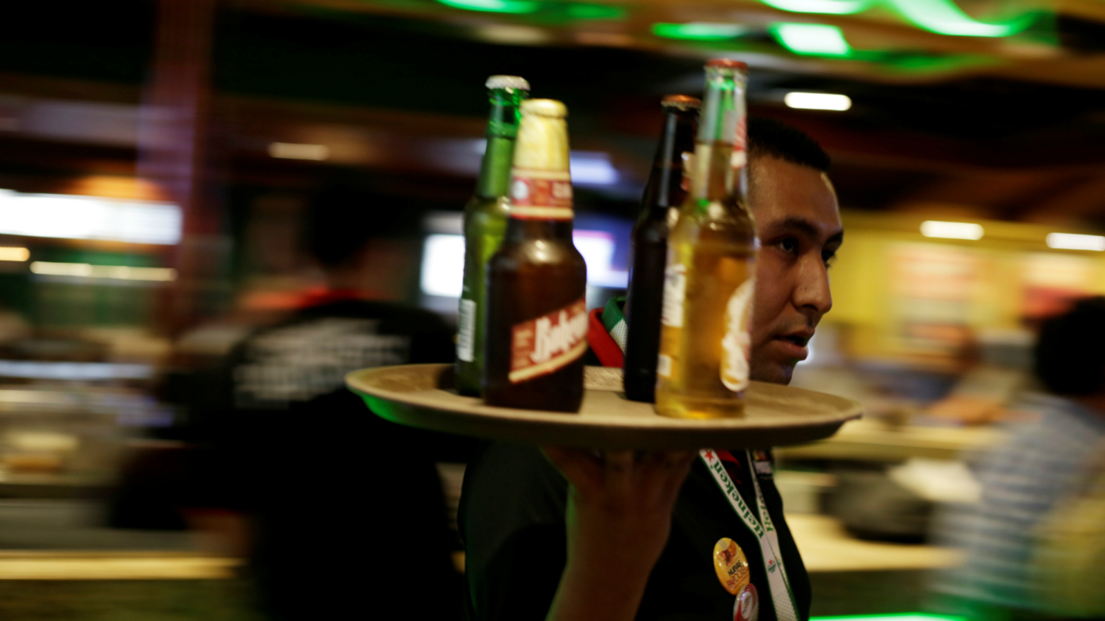 A waiter carries a tray with bottles of beer at a bar in Ciudad Juarez, Mexico June 20, 2017. Picture taken June 20, 2017.