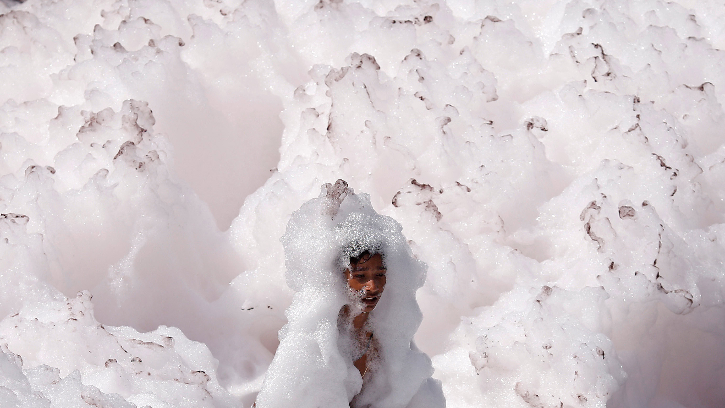 A boy plays in the foam, covering the polluted water of the river Yamuna in New Delhi, India March 25, 2018. REUTERS/Adnan Abidi - RC19E9801E00