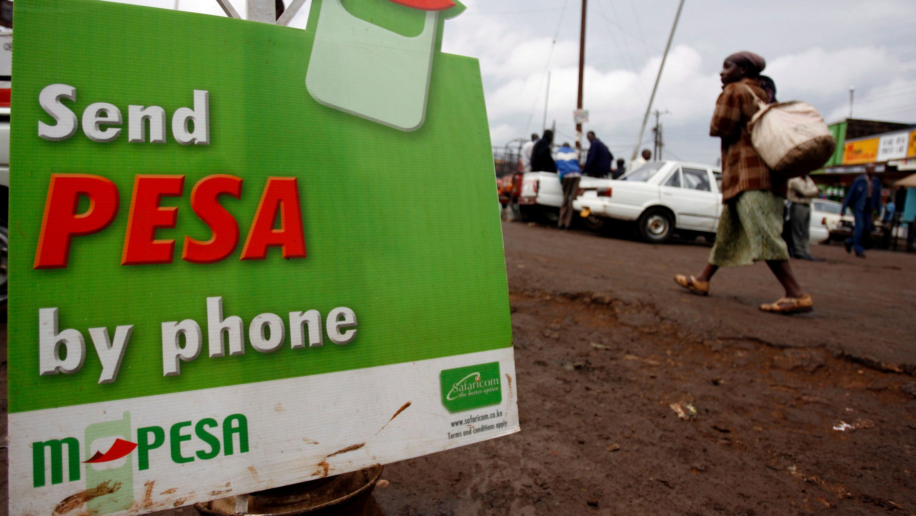 A woman walks past a sign advertising Safaricom mobile money called MPESA in the high density suburb of Kangami in Nairobi, Kenya on 26 March 2008. The Kenyan government plans to sell 25 per cent of its stake in the highly profitable mobile operator Safaricom by holding east Africa's largest ever IPO which is scheduled to begin selling shares on 28 December 2008.