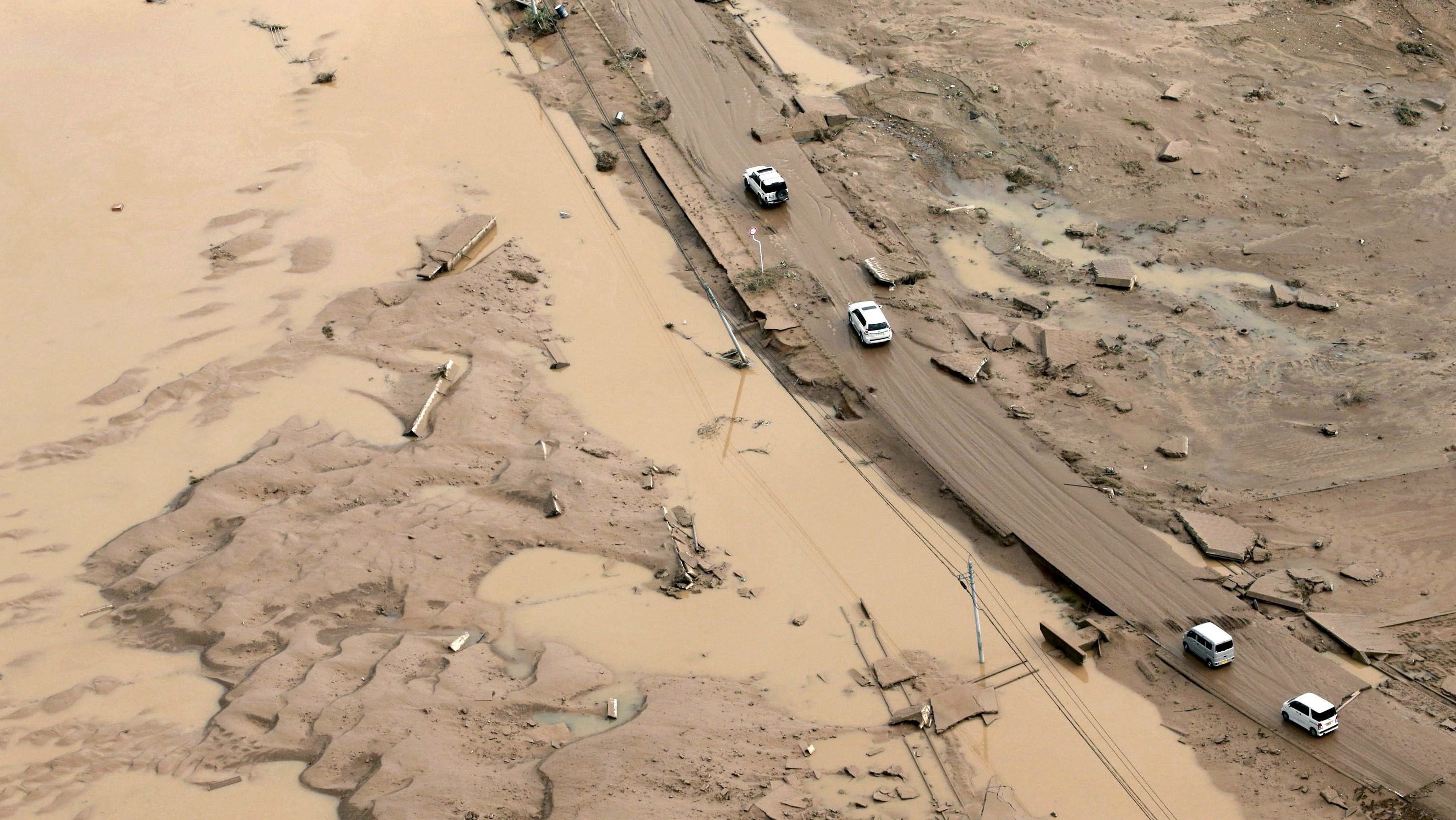 Cars move along a road covered with mud after heavy rain in Mabi town in Kurashiki
