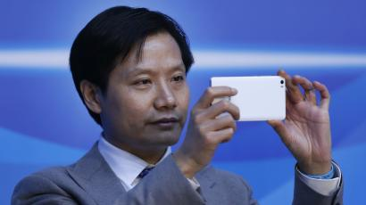 Lei Jun, founder and chief executive officer of Xiaomi, uses a phone during a session of the second annual World Internet Conference in Wuzhen town of Jiaxing, Zhejiang province, China