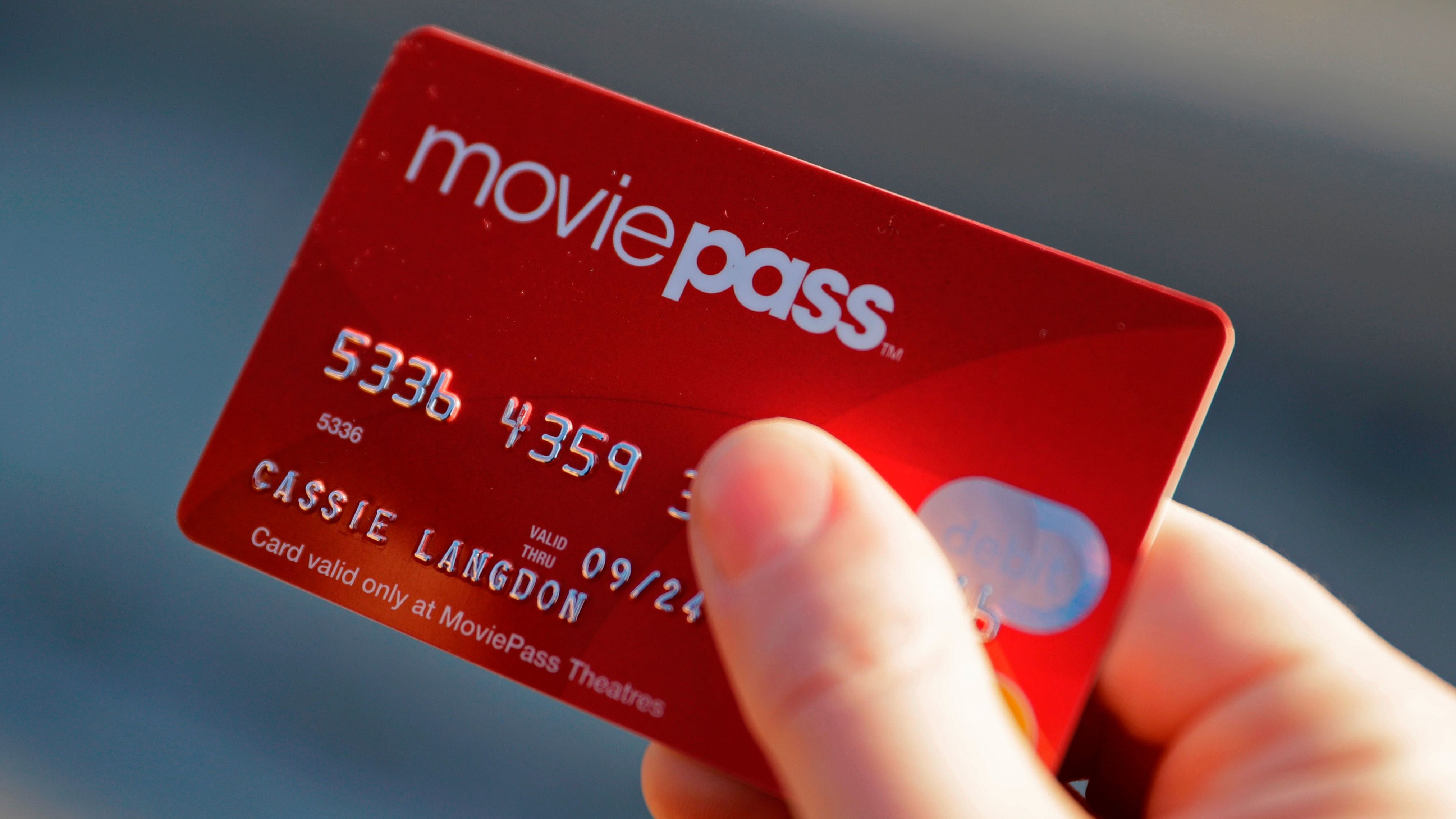 FILE - In this Jan. 30, 2018 file photo, Cassie Langdon holds her MoviePass card outside AMC Indianapolis 17 theatre in Indianapolis. The startup that lets customers watch a movie a day at theaters for just $10 a month, is limiting new customers to just four movies a month. The move comes as customers and industry experts question the sustainability of MoviePass' business model. Because MoviePass is paying most theaters the full price of the ticket, the service is in the red with just one or two movies in a month. (AP Photo/Darron Cummings, File)
