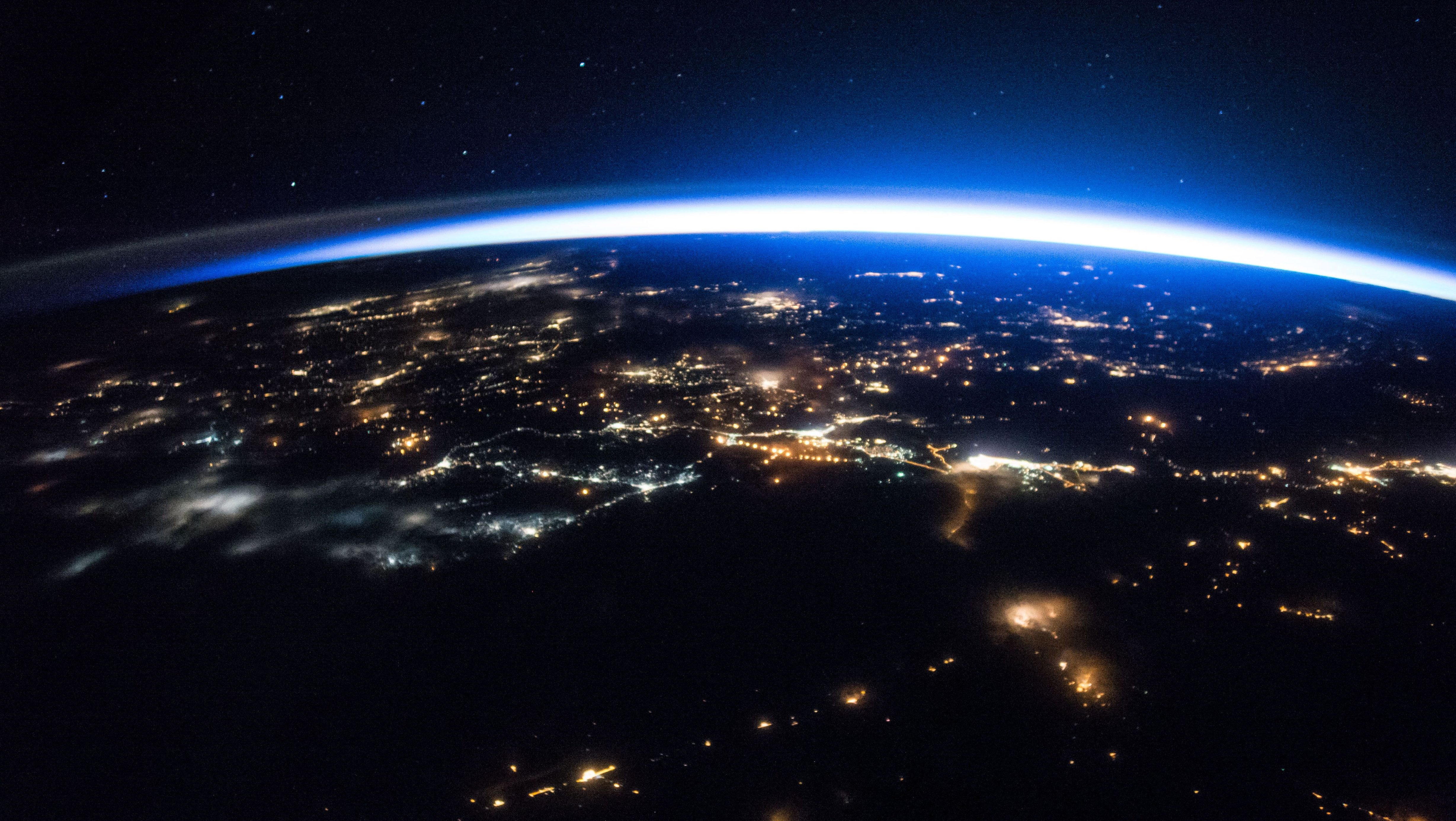 The International Space Station continues its orbit around the Earth as Expedition 50 astronauts captured this night image of sparkling cities and a sliver of daylight framing the northern hemisphere.