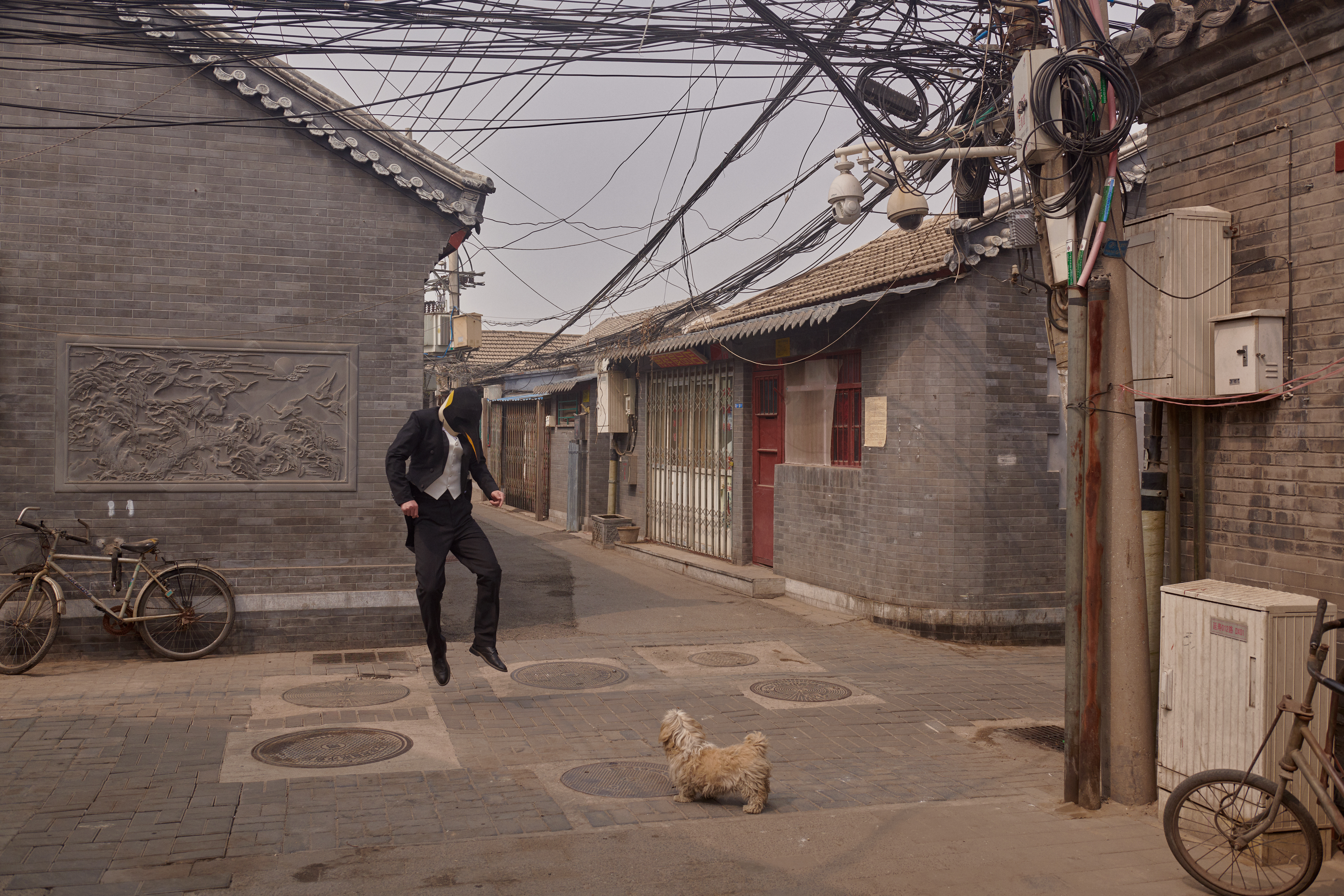This photo shows a hutong, a traditional courtyard residential compound in Beijing. CCTVs are also visible.