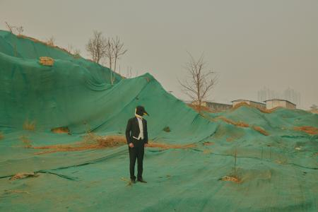 This picture showing the penguin man standing ono a construction site shows how development is constant in Beijing, said Xu. The green sheets covering the mounds of sand resemble man-made mountains.