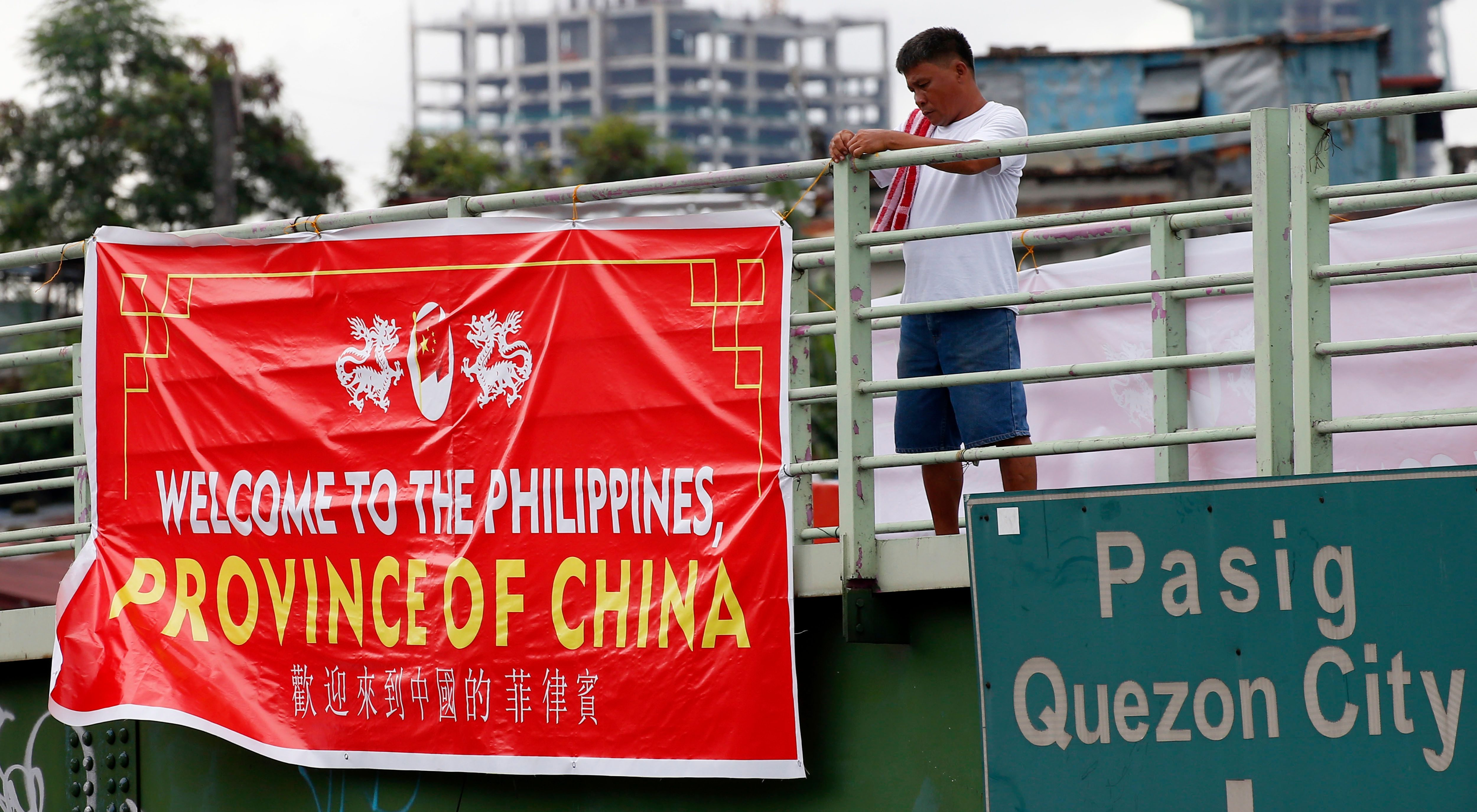 """A man tries to remove a tarpaulin banner with the words """"Welcome to the Philippines, Province of China"""" that was hung from an overpass Thursday, July 12, 2018, in Manila, Philippines. Similar banners have been seen in Manila Thursday which coincided with the second anniversary of the United Nations Permanent Court of Arbitration's decision upholding the Philippines' territorial rights on some islands, shoals, and reefs in the disputed Spratlys Group of islands in the South China Sea. The decision was shelved by President Rodrigo Duterte and was never recognized by China."""