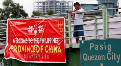 A Man Tries To Remove Tarpaulin Banner With The Words Welcome Philippines
