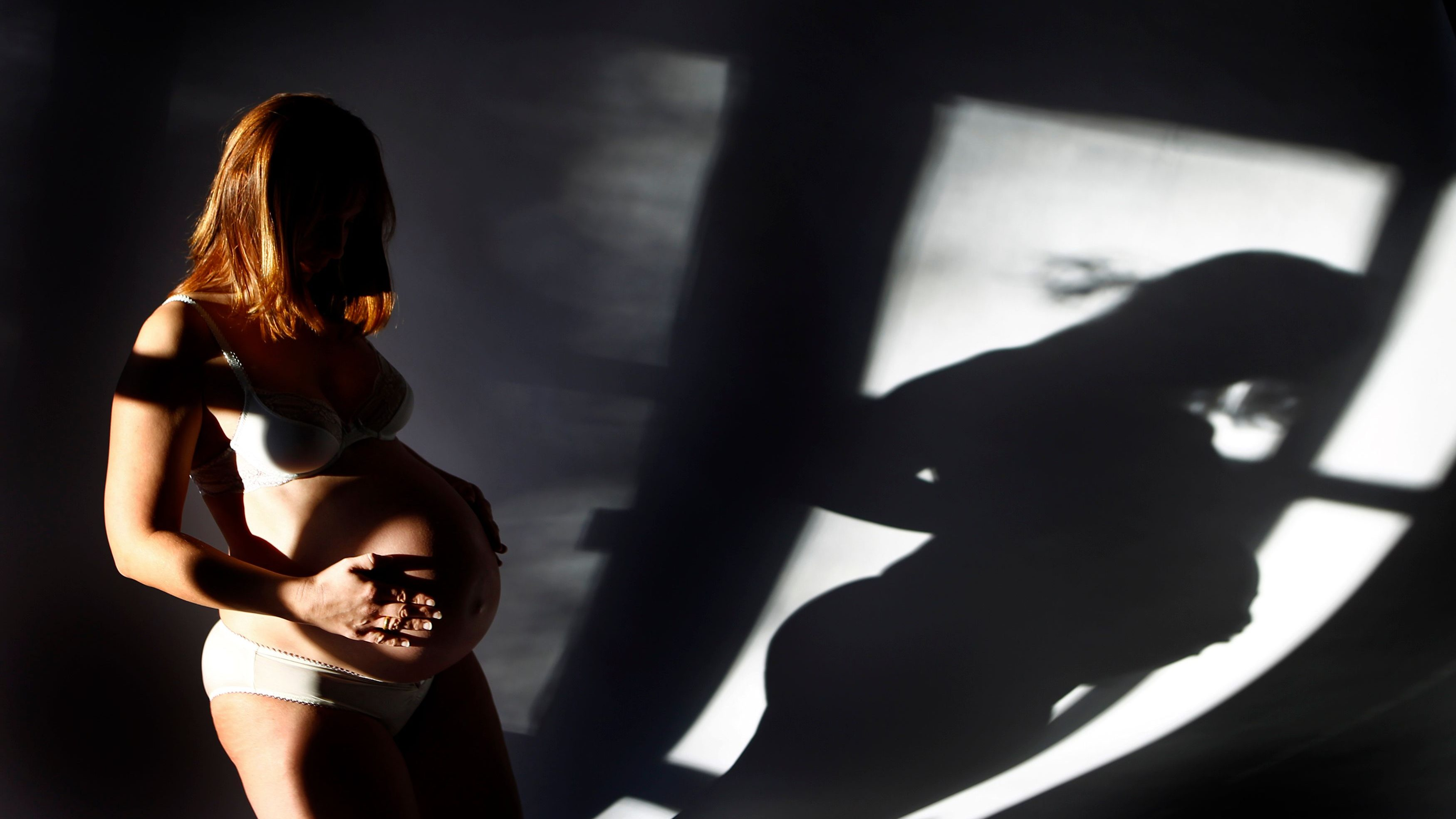 A woman in shadows holding her pregnant belly.