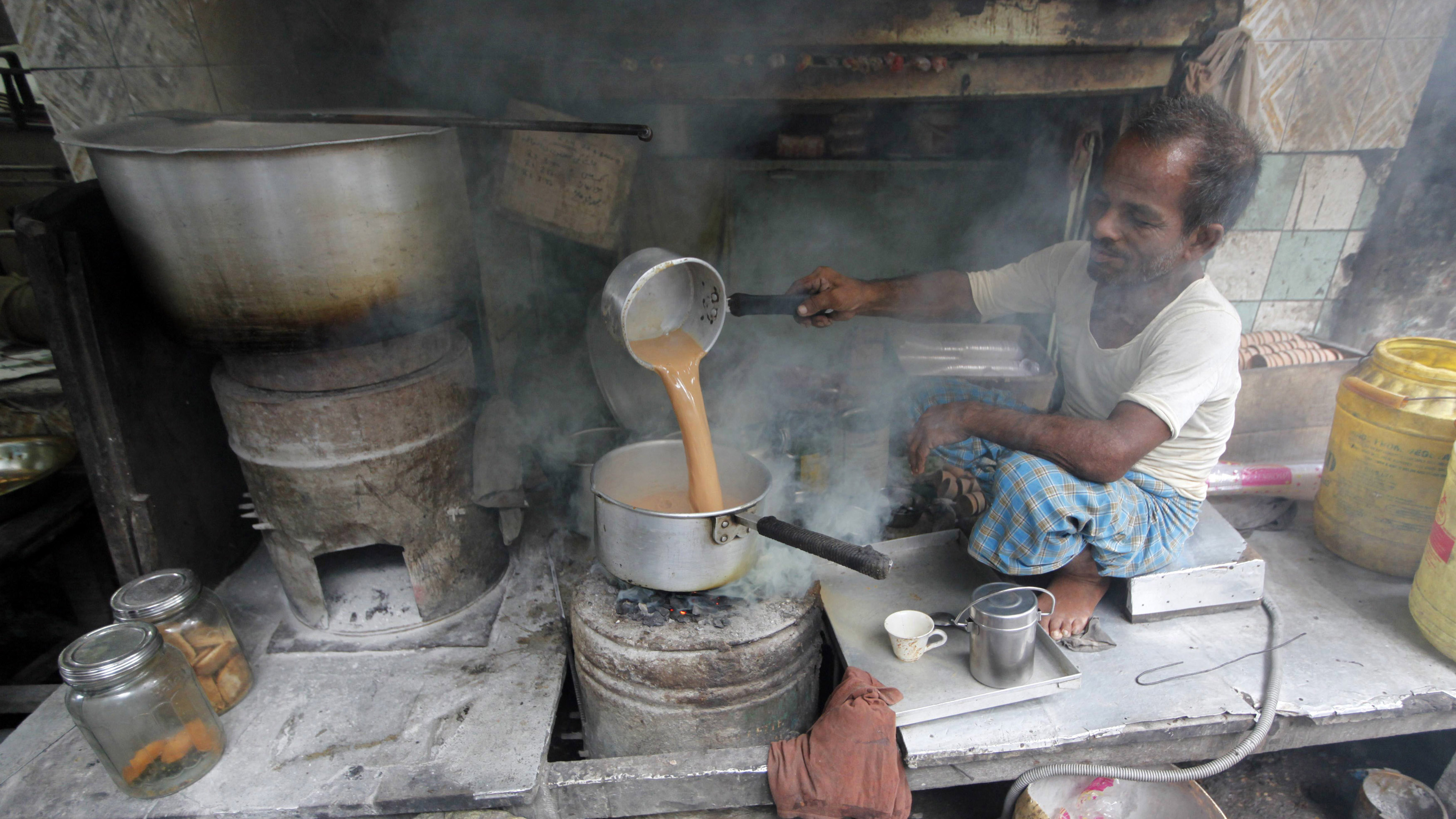 A tea stall holder prepares tea on a charcoal stove for his customers along a roadside in Kolkata June 29, 2011.   REUTERS/Rupak De Chowdhuri (INDIA - Tags: SOCIETY EMPLOYMENT BUSINESS) - GM1E76T1H6P01