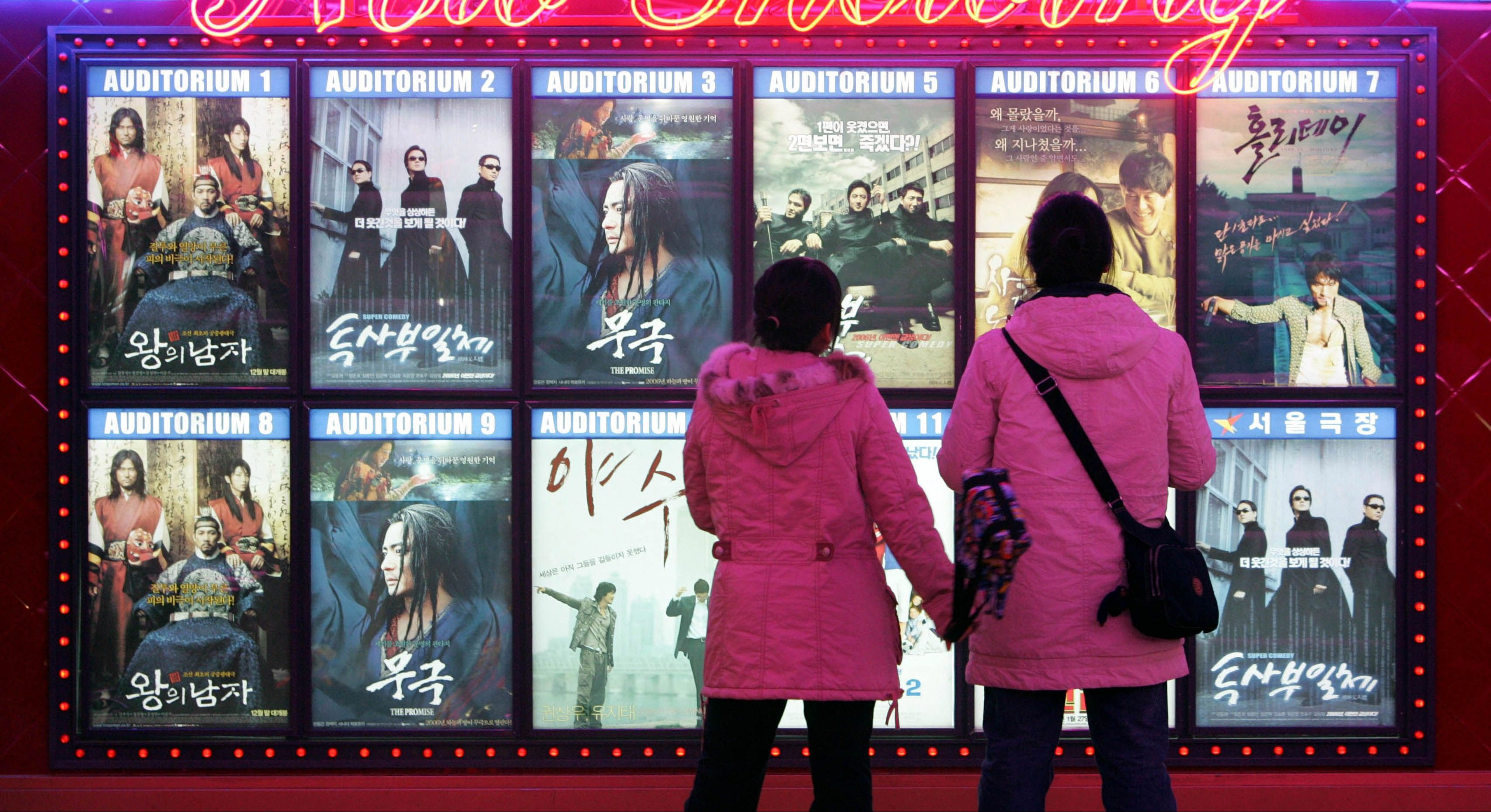 South Korean students look at movie posters at a theater in Seoul Thursday, Jan. 26, 2006. Hollywood is going to get greater access to South Korea's movie market after the government said Thursday it will cut in half the quota of homegrown films that must be shown in the country's cinemas. The United States had denounced the quota system as an unfair trade practice and major hurdle as the two countries move toward starting negotiations on a free trade agreement.