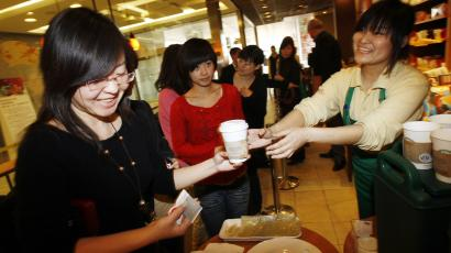 A Starbucks staff member hands out free coffee to customers at an event to mark the 10th anniversary of Starbucks' launch in China, at the the company's original outlet in Beijing Wednesday, Jan. 14, 2009. The Coffee chain Starbucks has started producing coffee grown by farmers in China and hopes to bring the blend to stores all over the world.