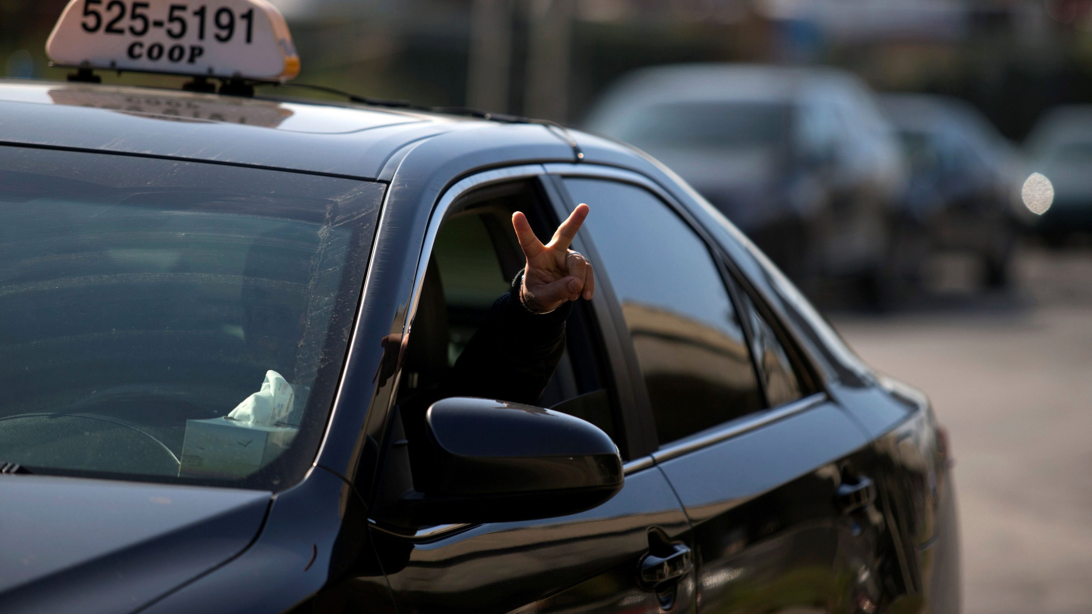 A taxi driver flashes a peace sign as he and other taxi drivers begin their protest against Uber in Montreal, Canada October 5, 2016. REUTERS/Christinne Muschi - D1BEUFGHFOAA