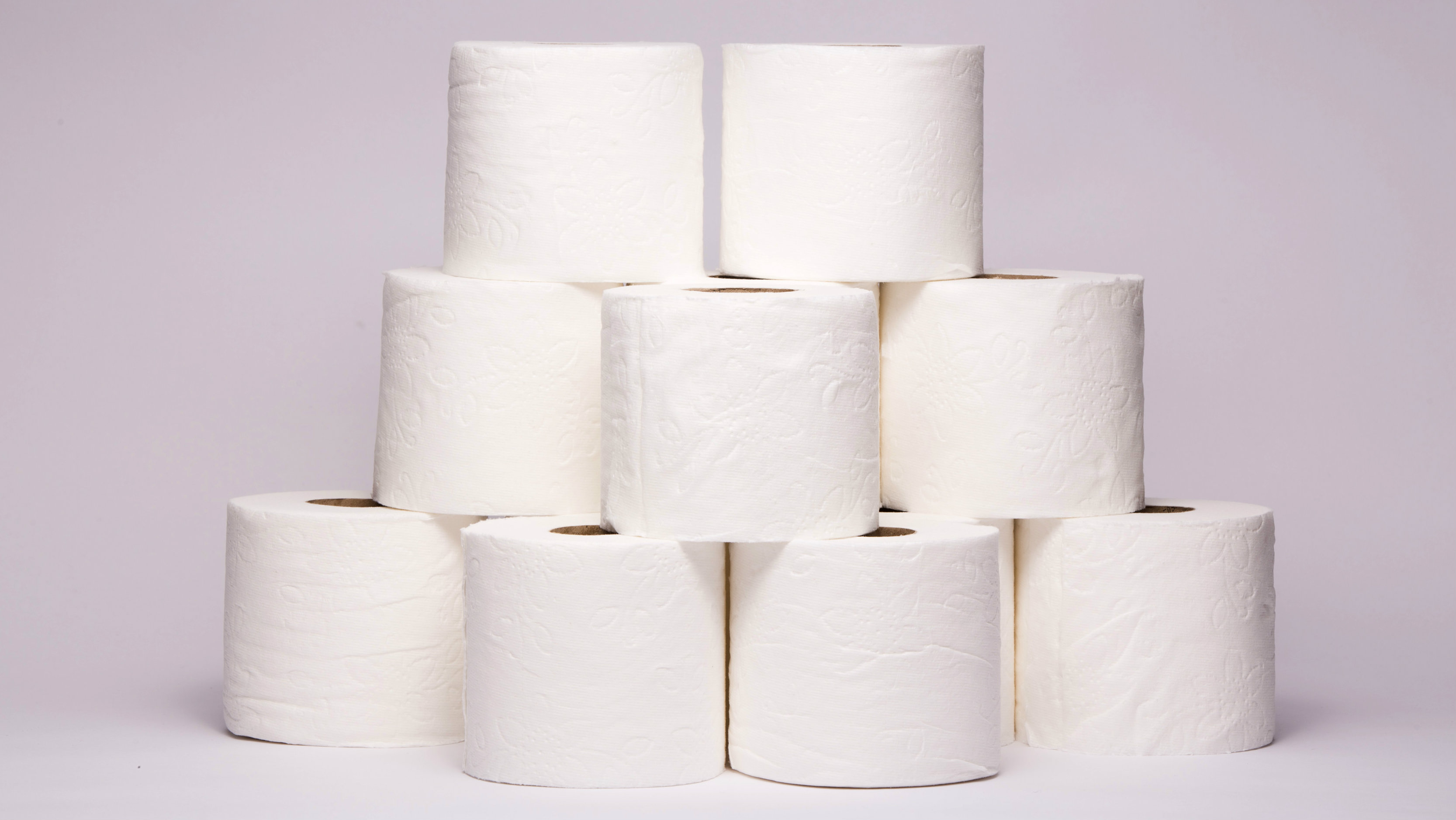 A stack of toilet paper against a neutral background.