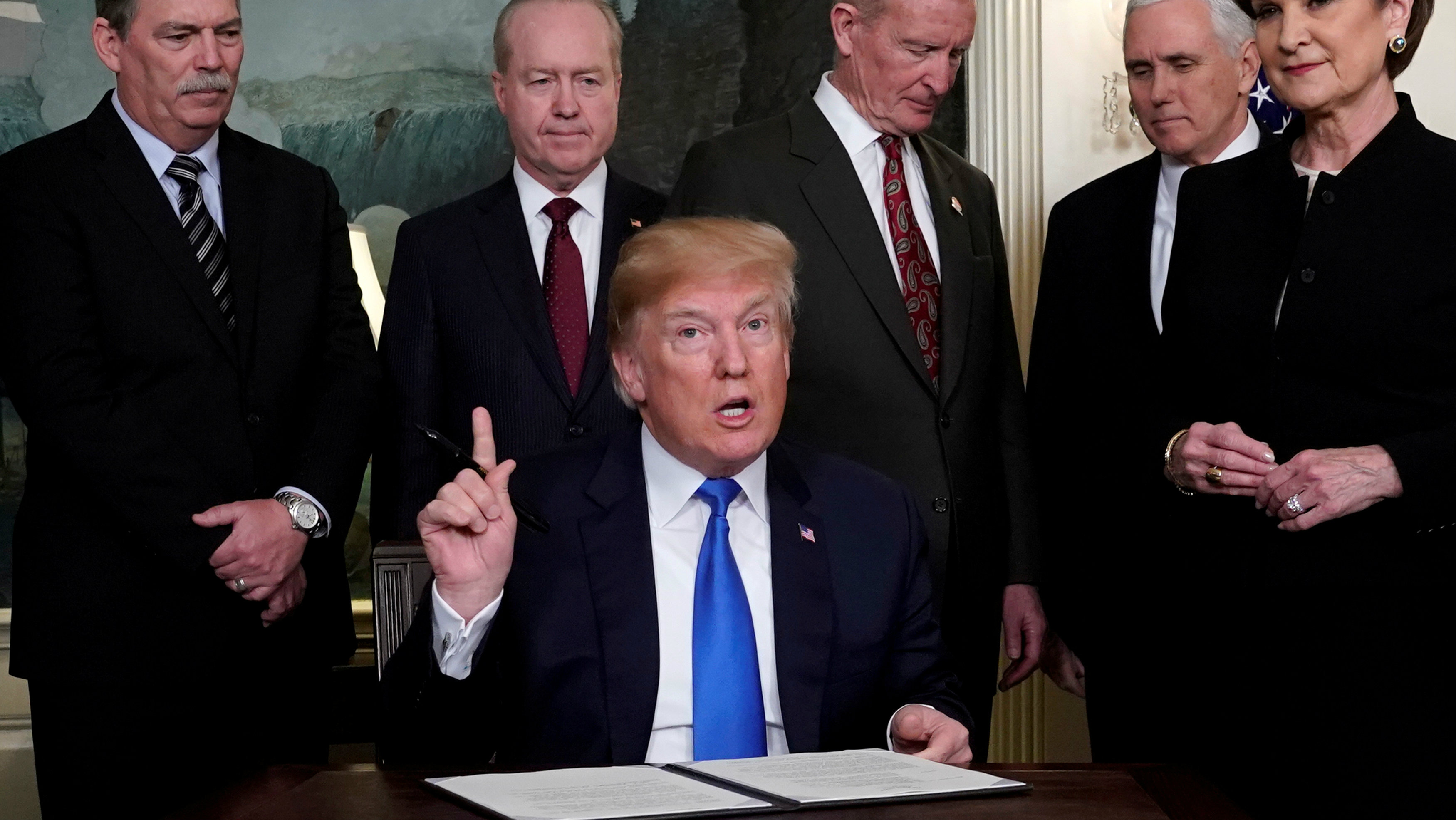 Donald Trump, surrounded by business leaders and administration officials, prepares to sign a memorandum on intellectual property tariffs