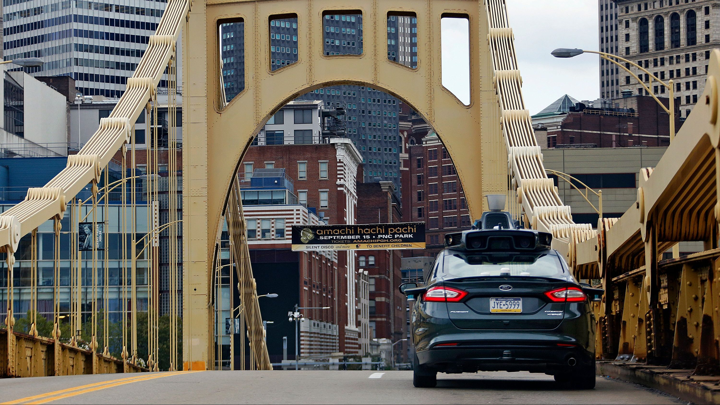 A self driving Uber car drives across the ninth street bridge in downtown Pittsburgh Wednesday, Sept. 14, 2016. On Wednesday, a fleet of self-driving Ford Fusions began picking up Uber riders who opted to participate in a test program. While the vehicles are loaded with features that allow them to navigate on their own, an Uber engineer sits in the driver's seat and can seize control if things go awry.  (AP Photo/Gene J. Puskar)