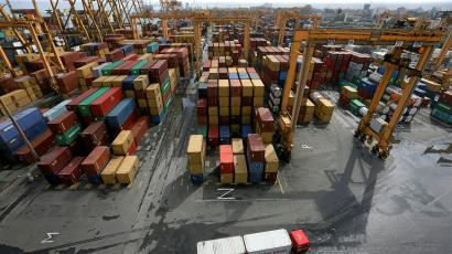 A container truck carries a container box past shipping containers at the main port in Colombo, Sri Lanka June 21, 2018.