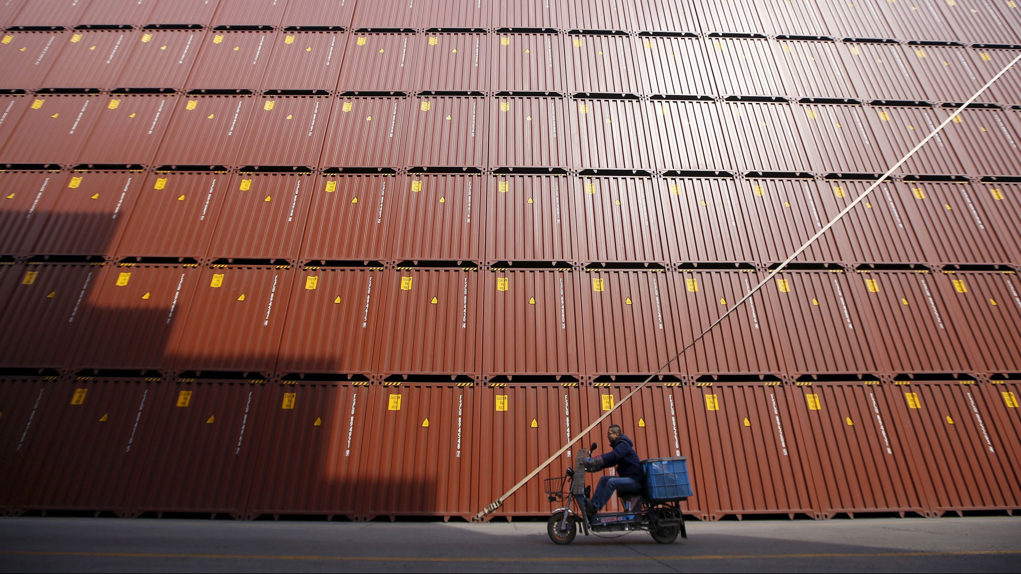 A man rides a vehicle past container boxes at a port in Shanghai