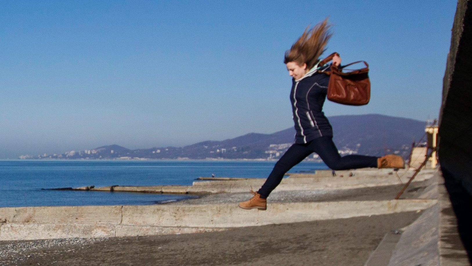 A woman jumps down onto the beach in the Adler district of Sochi