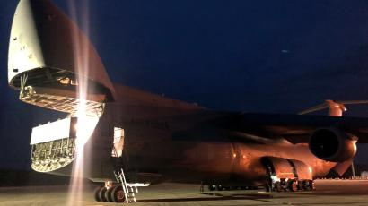 A US Air Force C-5 Galaxy opens its front cargo bay to begin unloading a protected communications satellite at Cape Canaveral Air Force Station, Florida.