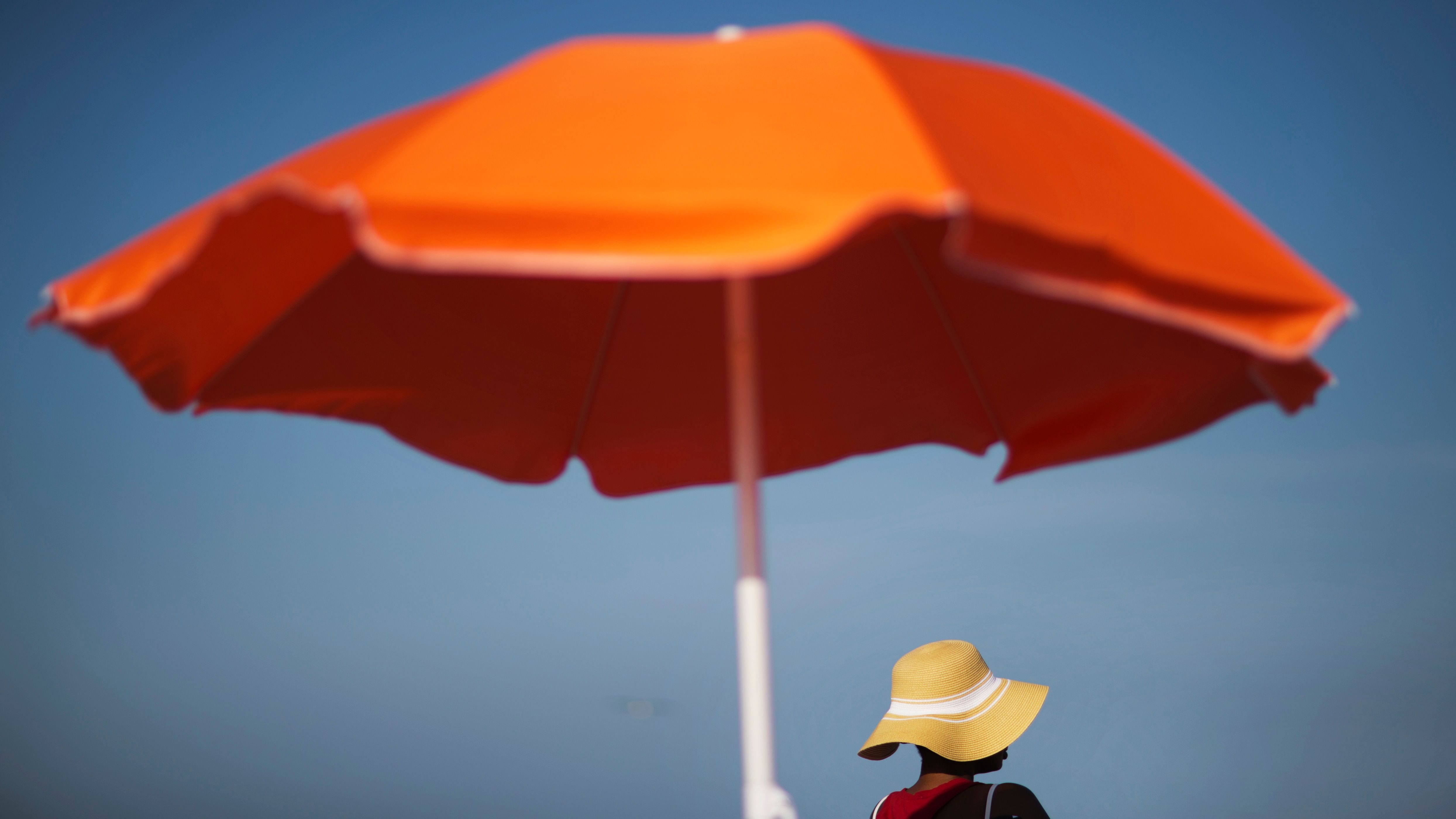 Someone in a brimmed hat sitting under a big orange umbrella