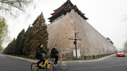 In this Wednesday, March 22, 2017 photo, people ride bicycles of bike-sharing companies Ofo, left, and Mobike, right, past a corner tower of the Forbidden City in Beijing, China. As many as 2.2 million of these two-wheelers have been deployed, which are available for rent for as little as U.S. 7 cents for half an hour, in the latest symbol of heavy spending in China's internet sector where startups are in a race to attract more users to their services.