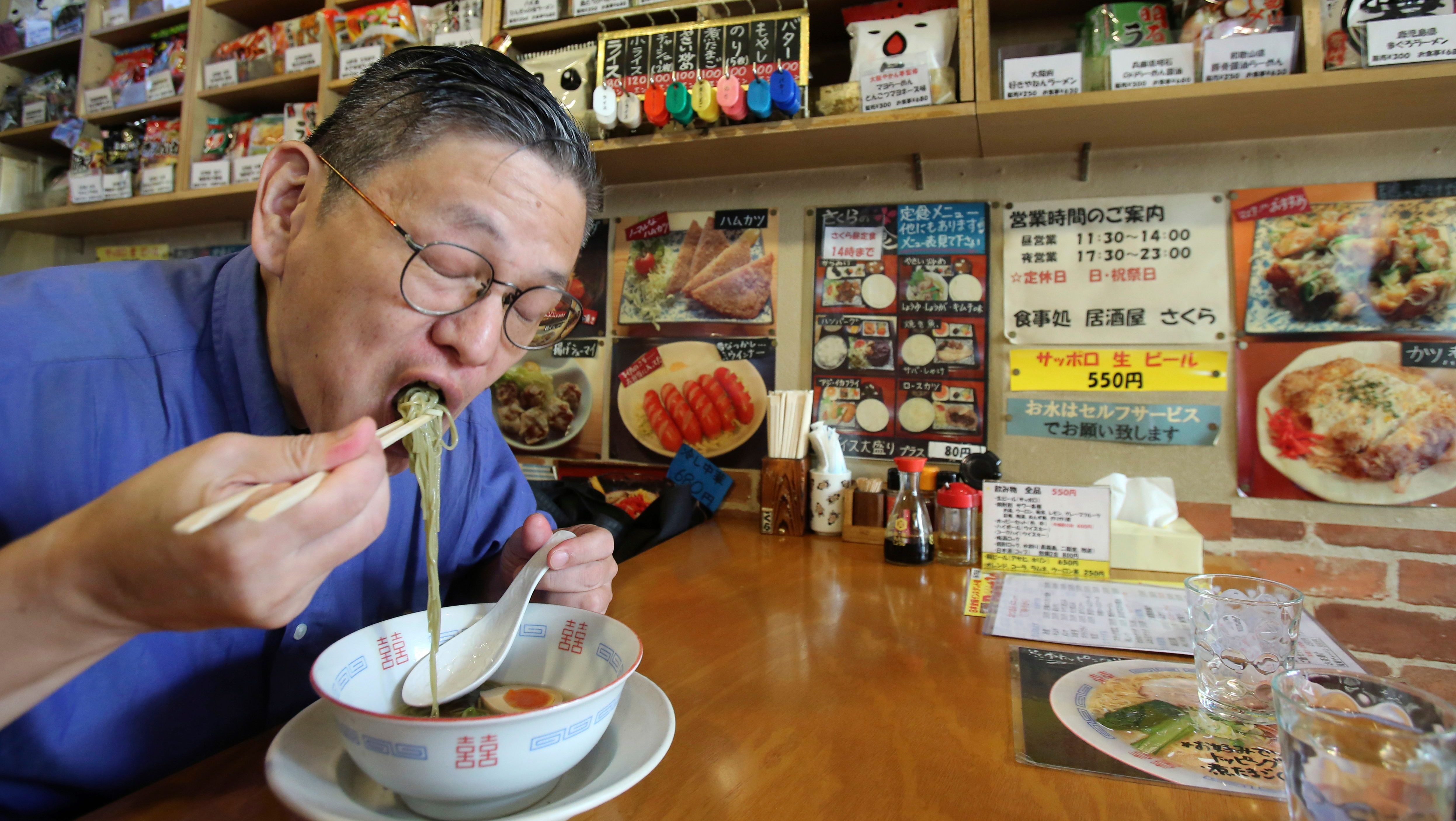 """In this 2014 photo, Japanese instant ramen noodle expert Masaya """"Sokusekisai"""" Oyama, 55, slurps noodles at a shop and restaurant specialized only in varieties of instant noodles in Tokyo."""