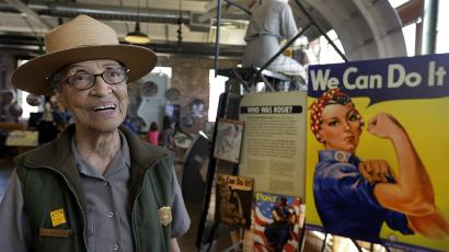 Park ranger Betty Soskin standing next to a Rosie the Riveter poster.