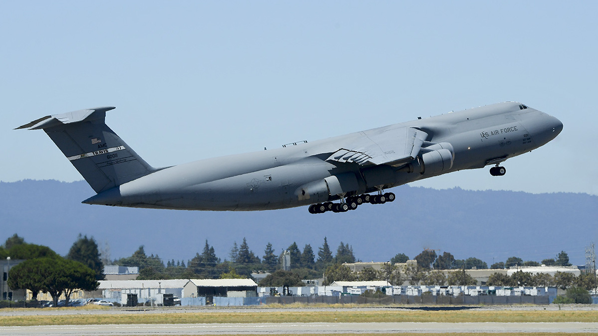 The C-5 containing 32 tons of satellite and equipment takes off at Moffett Field.