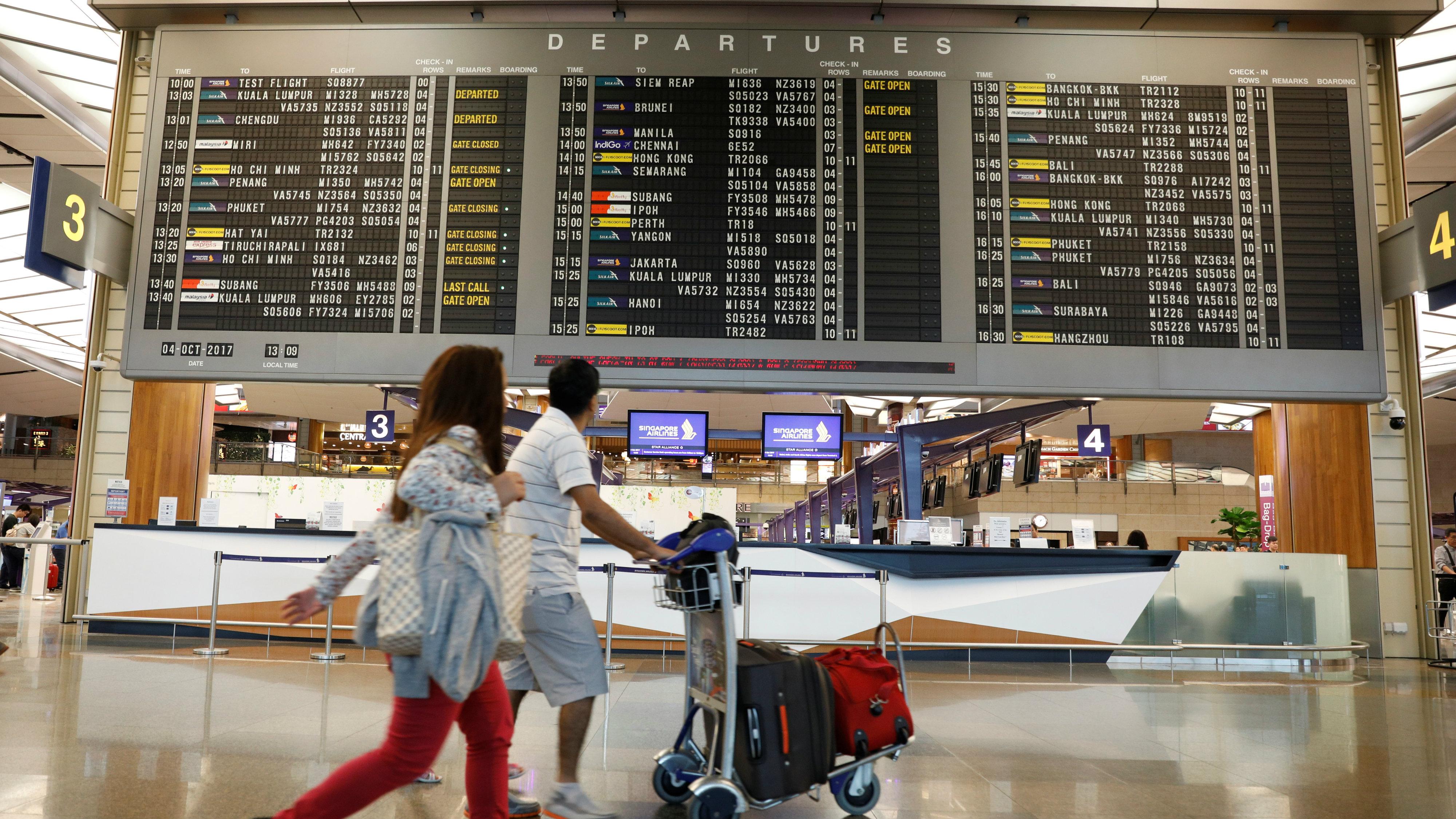 travelers walk past departures board