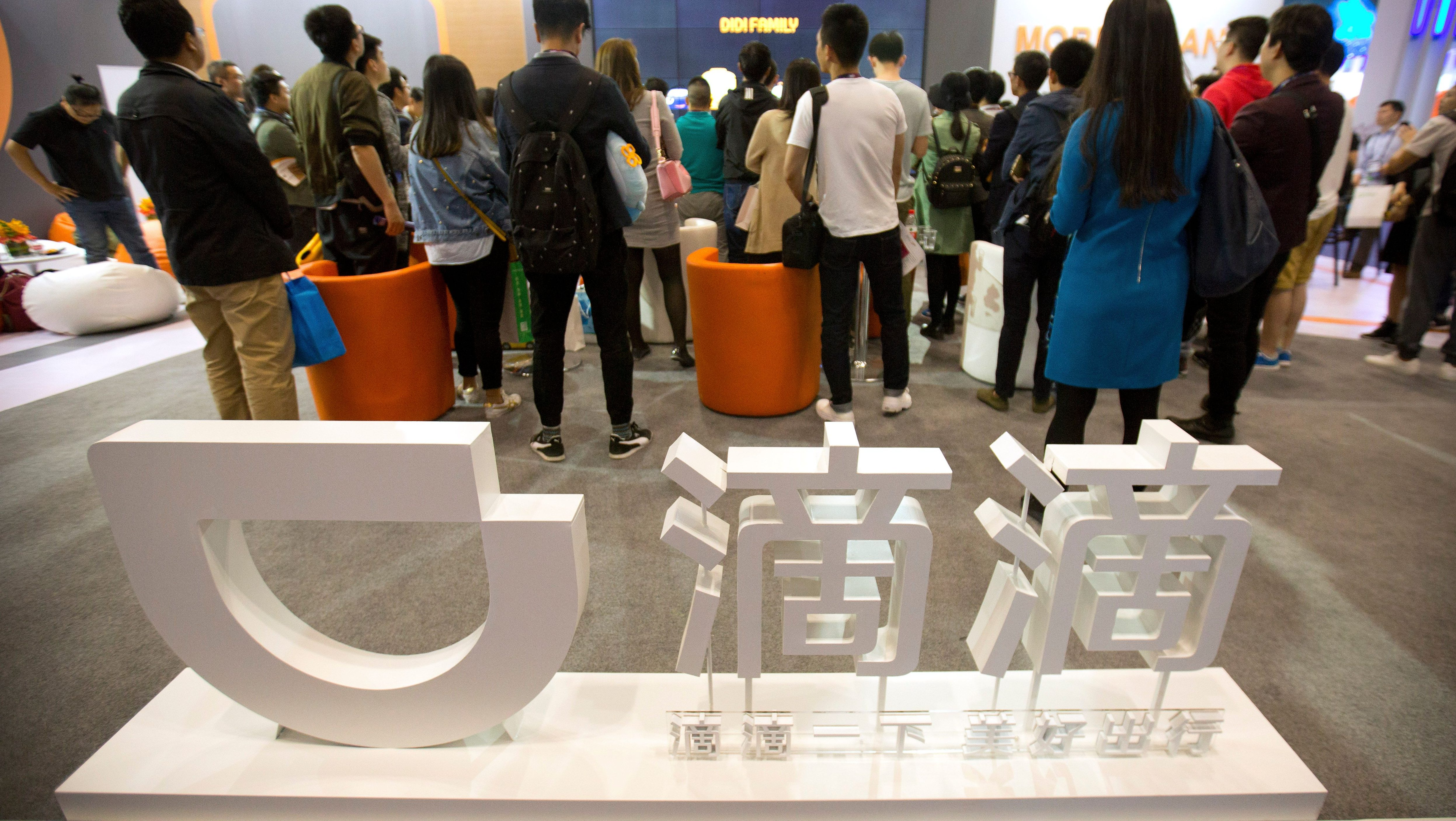 Visitors look at a display booth for Chinese ride-hailing service Didi Chuxing at the Global Mobile Internet Conference (GMIC) in Beijing, Thursday, April 27, 2017.