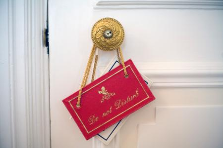 A 'Do not disturb' sign hanging on a doorknob at the Ritz Hotel, London (Photo by In Pictures Ltd./Corbis via Getty Images)