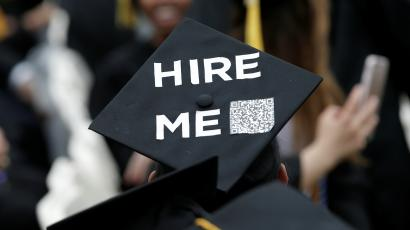 """An image of a student where a graduation cap that say """"hire me""""."""