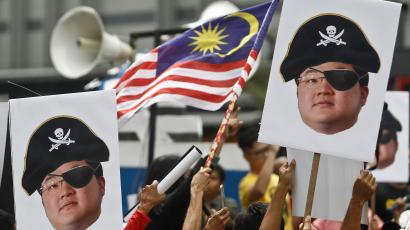Protesters hold portraits of Jho Low illustrated as a pirate during a protest in Kuala Lumpur, Malaysia, Saturday, April 14, 2018. Protesters gathered Saturday in Kuala Lumpur to call for the arrest of businessperson Jho Low over the alleged multibillion-dollar theft of funds from a Malaysian state investment company.