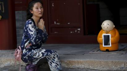 A visitor asks a temple staff to give her chance to take picture with robot Xian'er which is placed in the main building of Longquan Buddhist temple for photograph, on the outskirts of Beijing, April 20, 2016.
