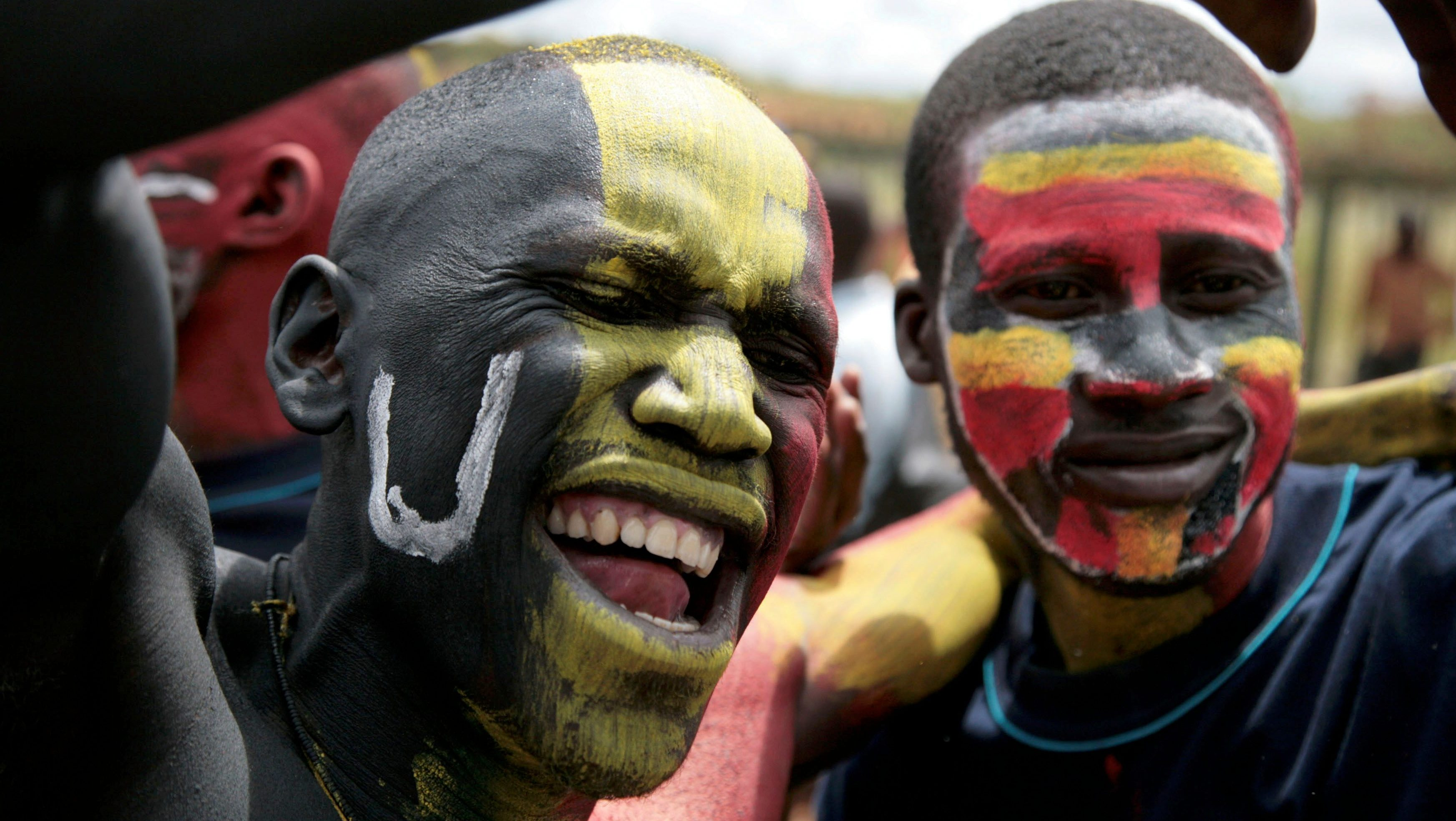 Fans painted in the colours of Uganda's national flag cheer before the start of the African Nations Cup Group Three qualifier soccer match between Uganda and Nigeria in Kampala June 2, 2007.