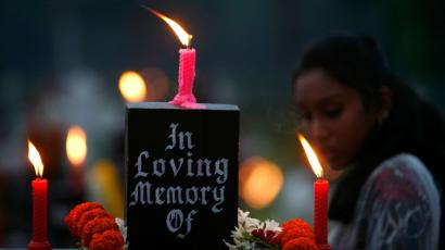 A woman stands beside the grave of her loved one in a cemetery during the observance of All Souls Day in Kolkata
