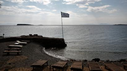 A Greek flag flutters at a beach southeast of Athens