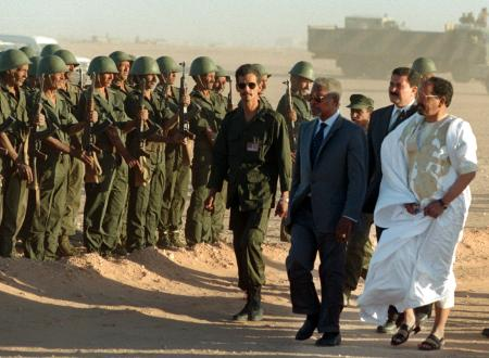 """United Nations Secretary-General Kofi Annan (C) reviews troops along with Polisario Front chief Mohamed Abdelaziz (R) upon arriving to a Polisario refugee camp in Smara, Western Sahara, November 30. Annan said after talks with Polisario Front leaders that he had won a """"clear yes"""" from them on his peace plan to resolve the long-running Western Sahara dispute. ES/CLH/ - RP1DRIFRGXAF"""