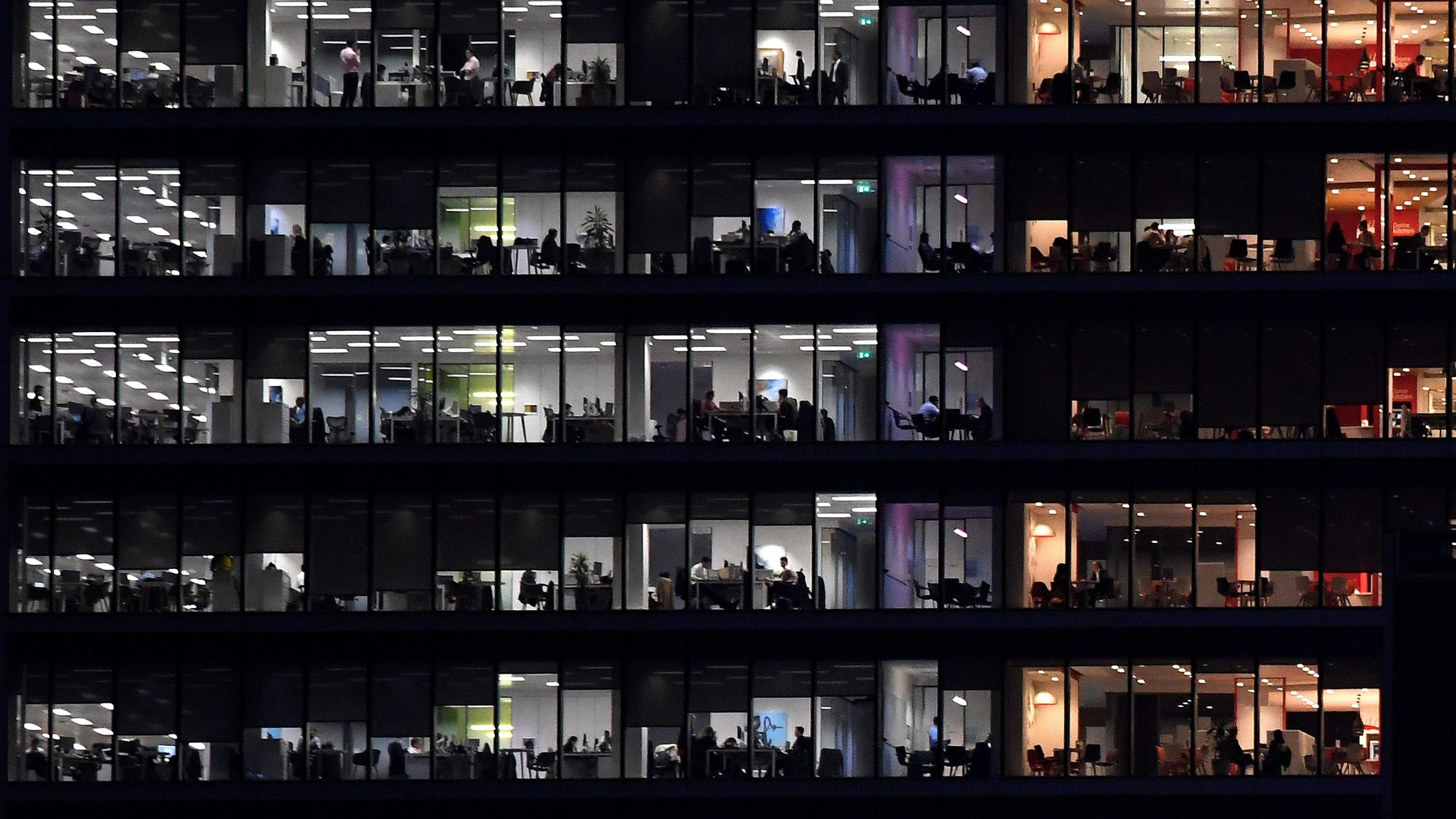 Workers are seen in an office tower