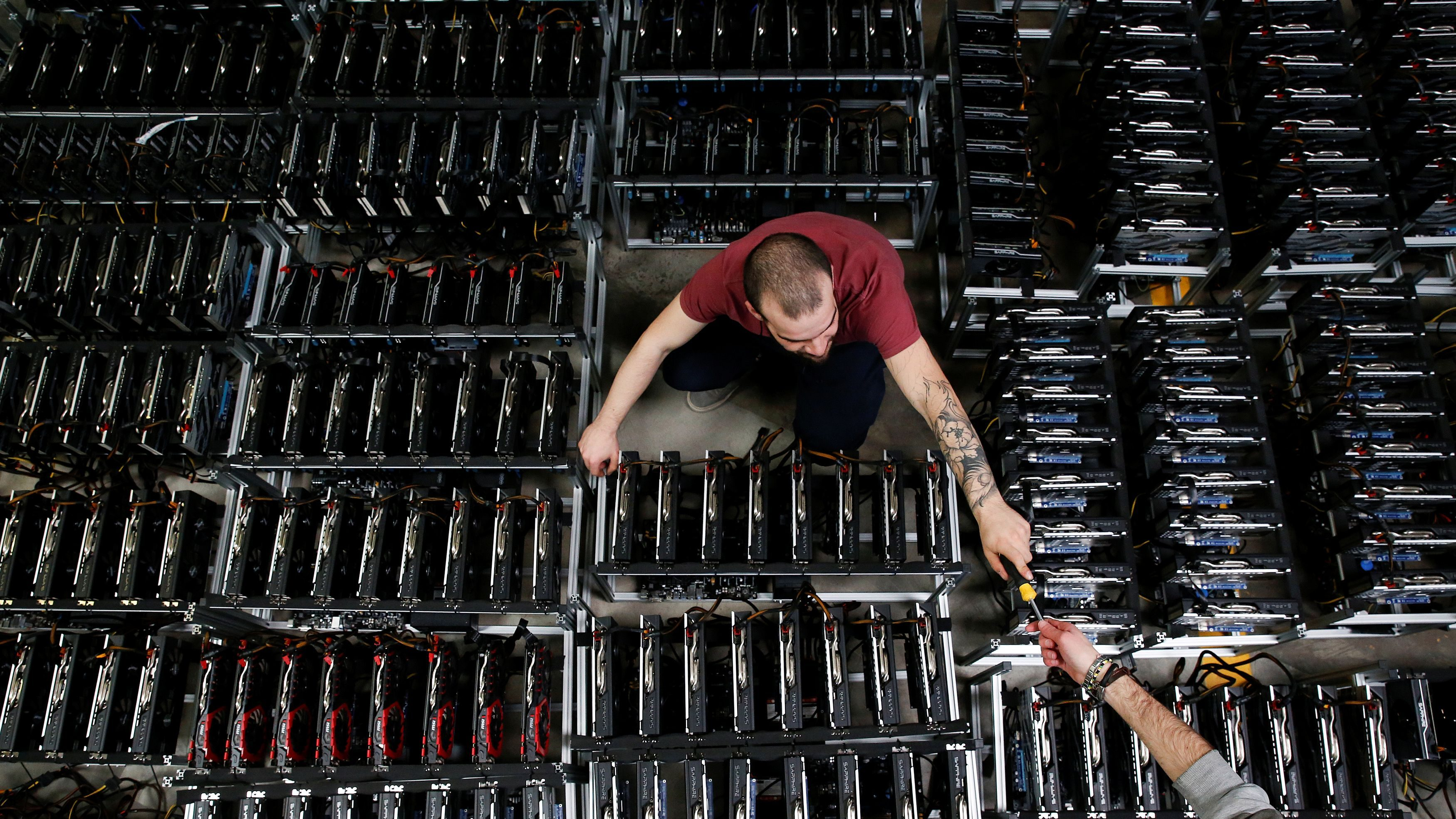 Employees work on bitcoin mining computers at Bitminer Factory in Florence