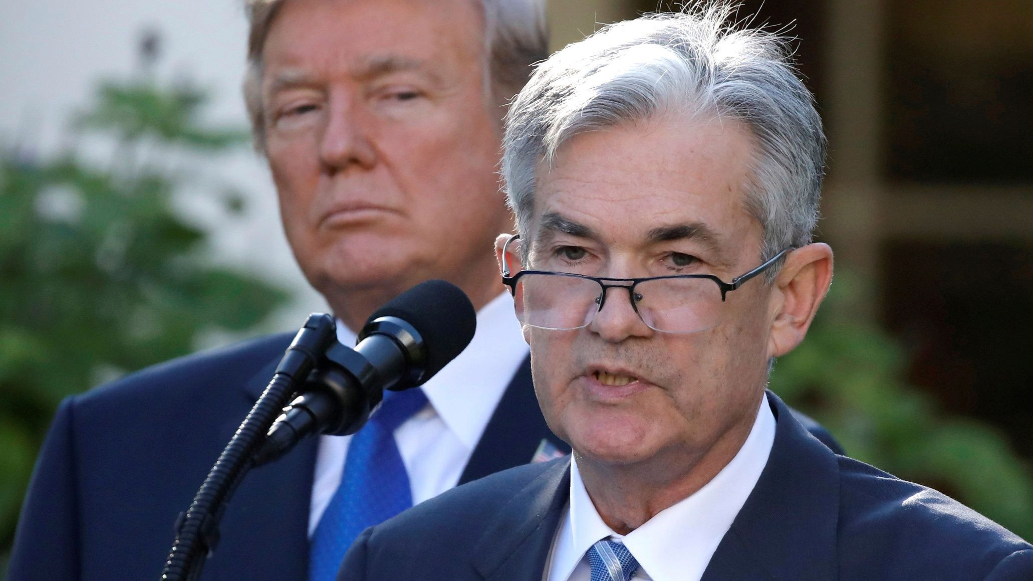 Federal Reserve chair Jay Powell speaks, with Donald Trump in the background