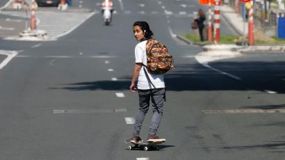 A girl skateboards on a street that was cleared by authorities during a protest against austerity measures by public sector workers, employees and trade union members in central Brussels