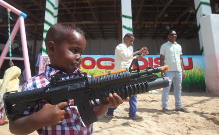 A Somali boy plays with a toy gun after prayers on the first day of Eid al-Adha in Somalia's capital Mogadishu, September 24, 2015. Muslims around the world celebrate Eid al-Adha to mark the end of the haj pilgrimage by slaughtering sheep, goats, camels and cows to commemorate Prophet Abraham's willingness to sacrifice his son, Ismail, on God's command.